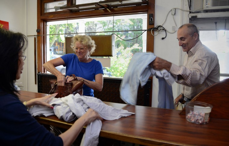Shirley Tsao, whose family owns TC Wing Laundry in Roland Park, chats at the counter with long-time customers Judy Kasper, left, and Gregg Bernstein, right.