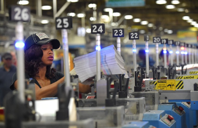 Rockelle Miller in the packaging area sorting the preprinted ads for the holiday paper. (Lloyd Fox/Baltimore Sun)