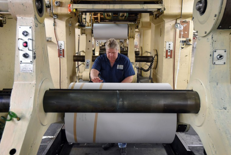 Bobby Helinski, a pressman at The Baltimore Sun Media Group's Port Covington printing plant, loads a roll of paper into the ground level of the printing press. (Lloyd Fox/Baltimore Sun)