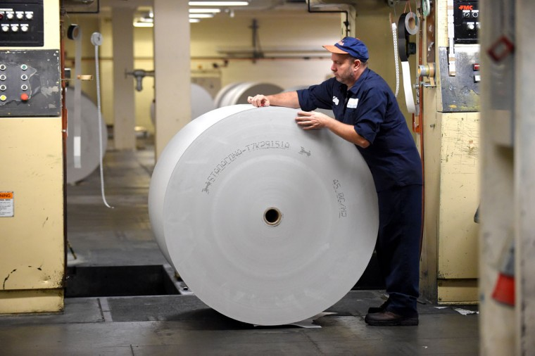 Thomas Samsel, a pressman at the Sun Park printing plant, prepares a roll of paper that each weigh one ton and are about 10 miles long. (Lloyd Fox/Baltimore Sun)