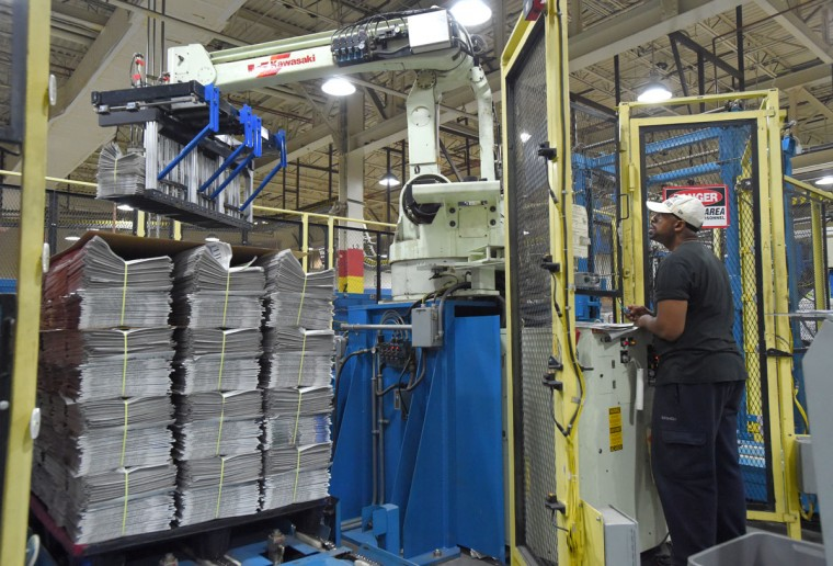 Chris Bonner keeps a watchful eye on the robotic stacker in the packaging area. (Lloyd Fox/Baltimore Sun)