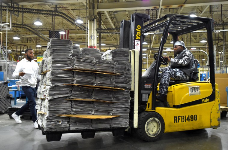 Quinn Richardson gets a pallet of papers ready for Adolph Morgan who takes them to be shrink wrapped and then loaded onto trucks for delivery. (Lloyd Fox/Baltimore Sun)