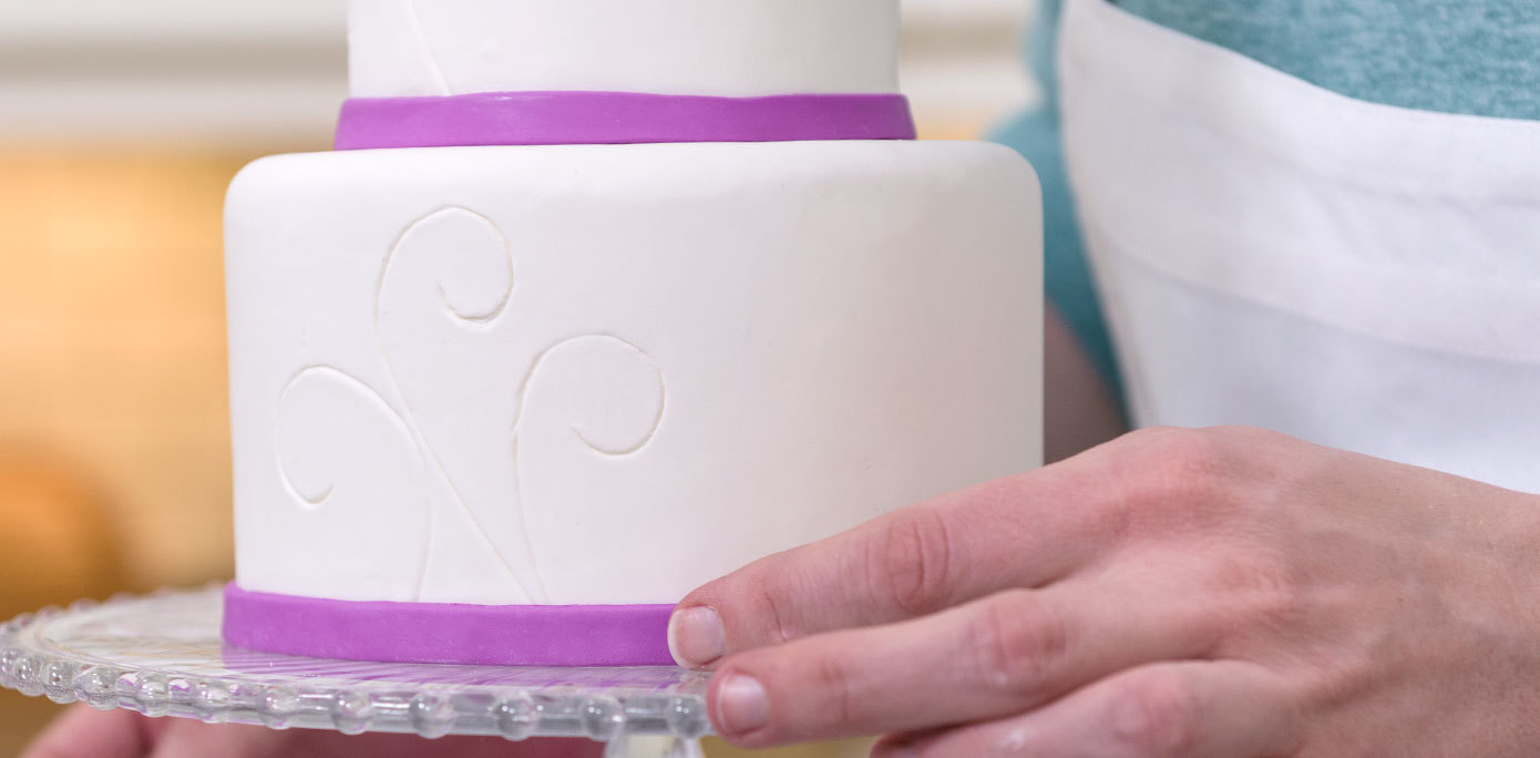 Apply purple fondants strips around the base of a Mother's Day butterfly cake