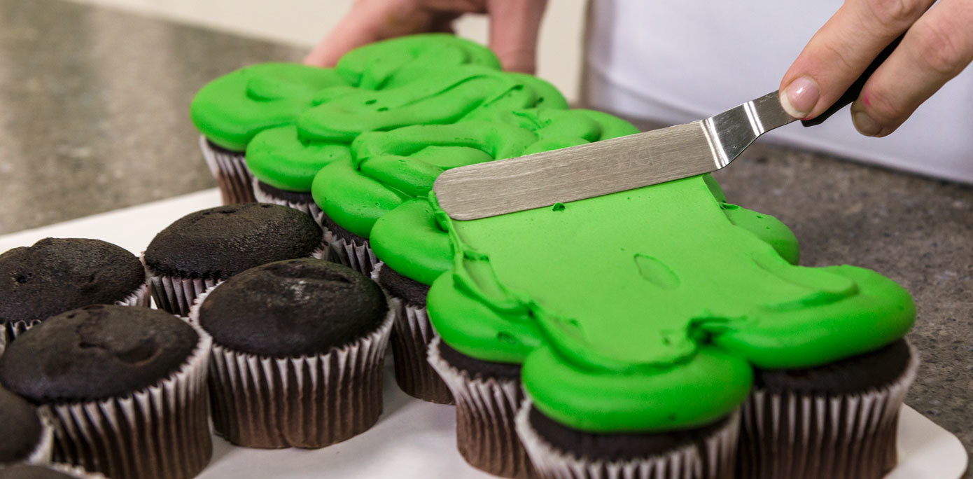 Pipe grass green icing onto the NFL cupcake cake