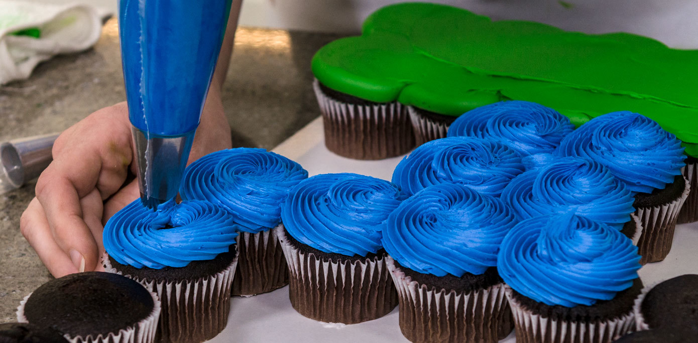 Pipe royal blue icing onto NFL goal post cupcakes