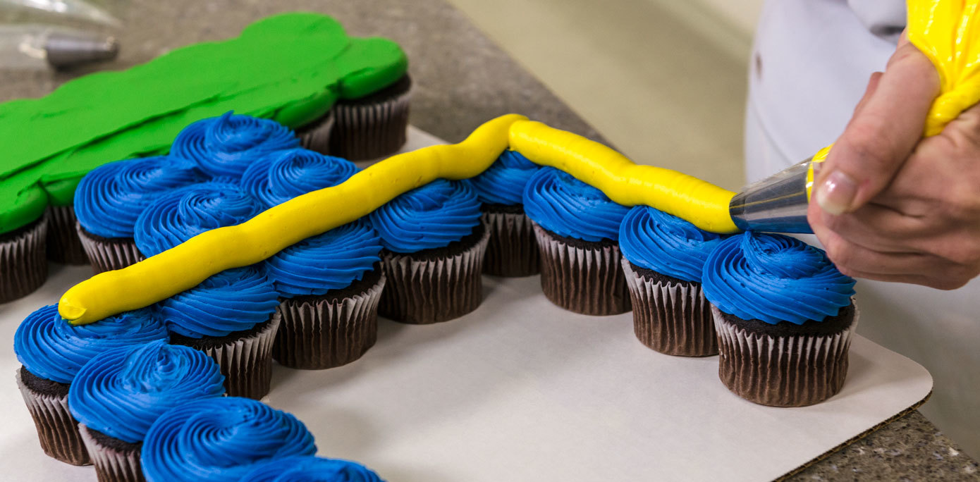 Pipe yellow icing onto NFL goal post cupcakes