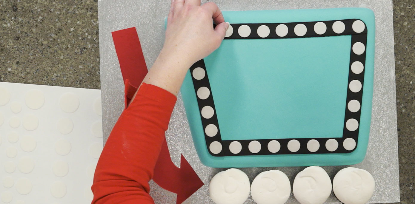 Attaching fondant to cake