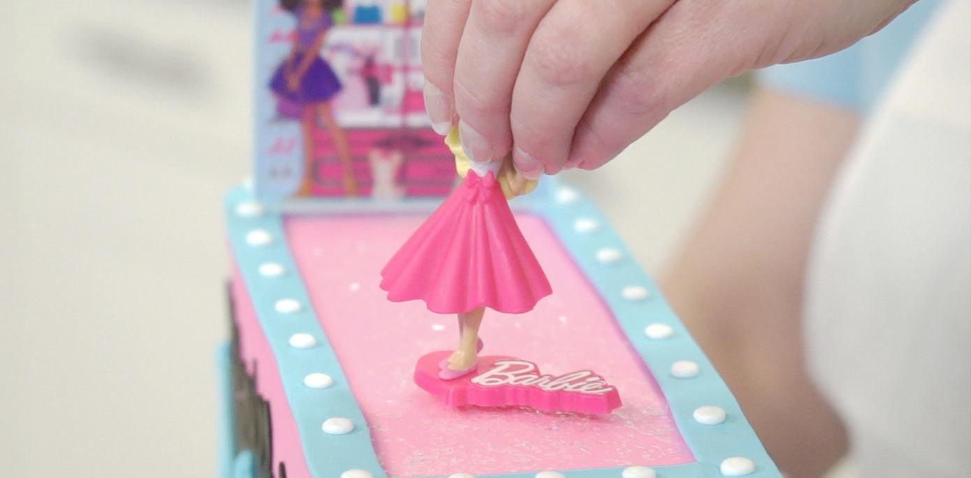 Adding Barbie to cake