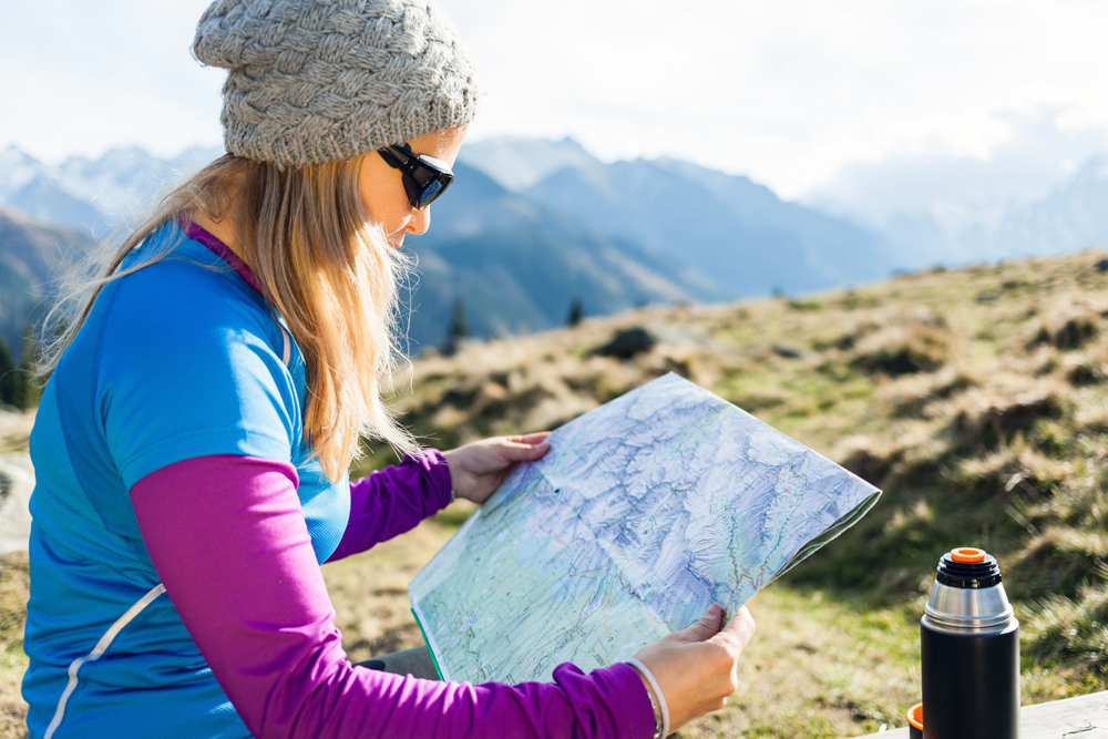 Best Hiking Gps Tracker 24265485 Young Woman Hiker Reading Map In Mountains  On Trip