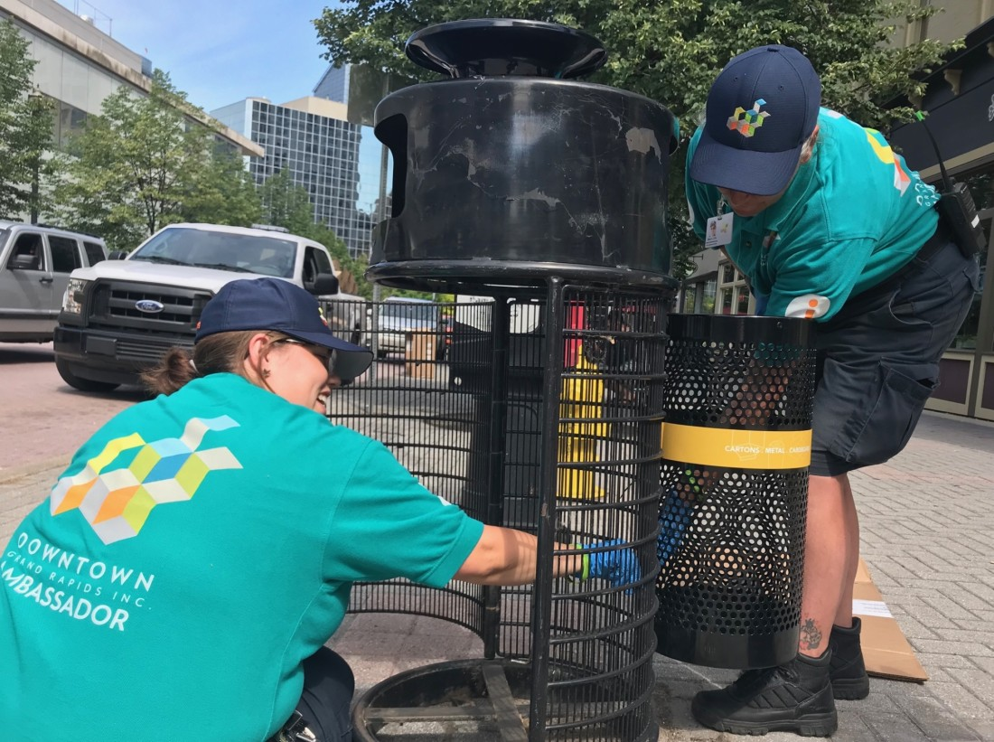 Downtown Ambassadors Rebecca install new recycling infrastructure on Monroe Center.