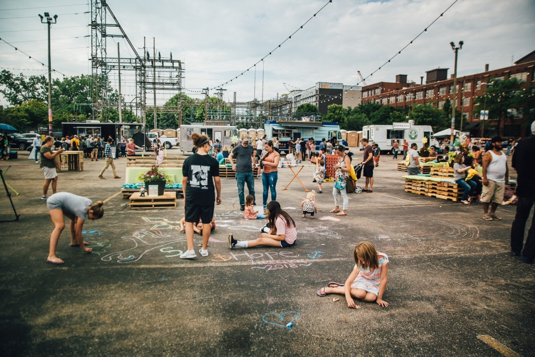 A formerly lifeless parking lot turned riverfront community gathering place in the Monroe North neighborhood.