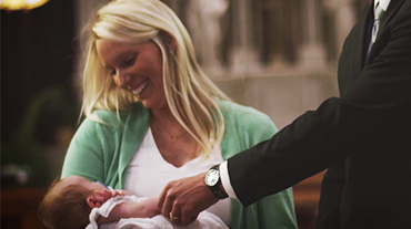 A couple holding their child before Baptism