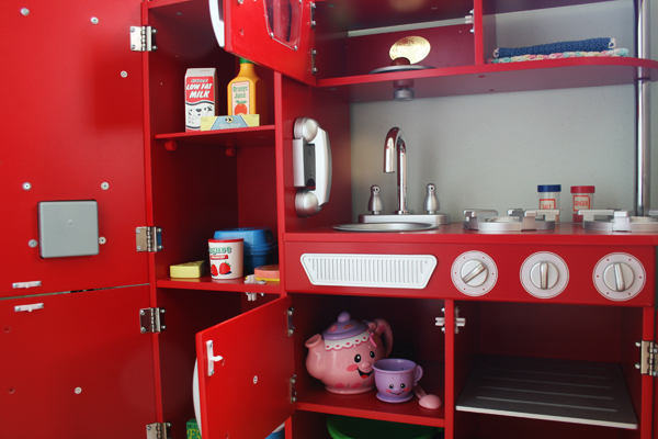Red retro play kitchen doors for storage. See more photos here: http://everclevermom.com/2013/09/evas-diy-pretend-market-and-play-kitchen/