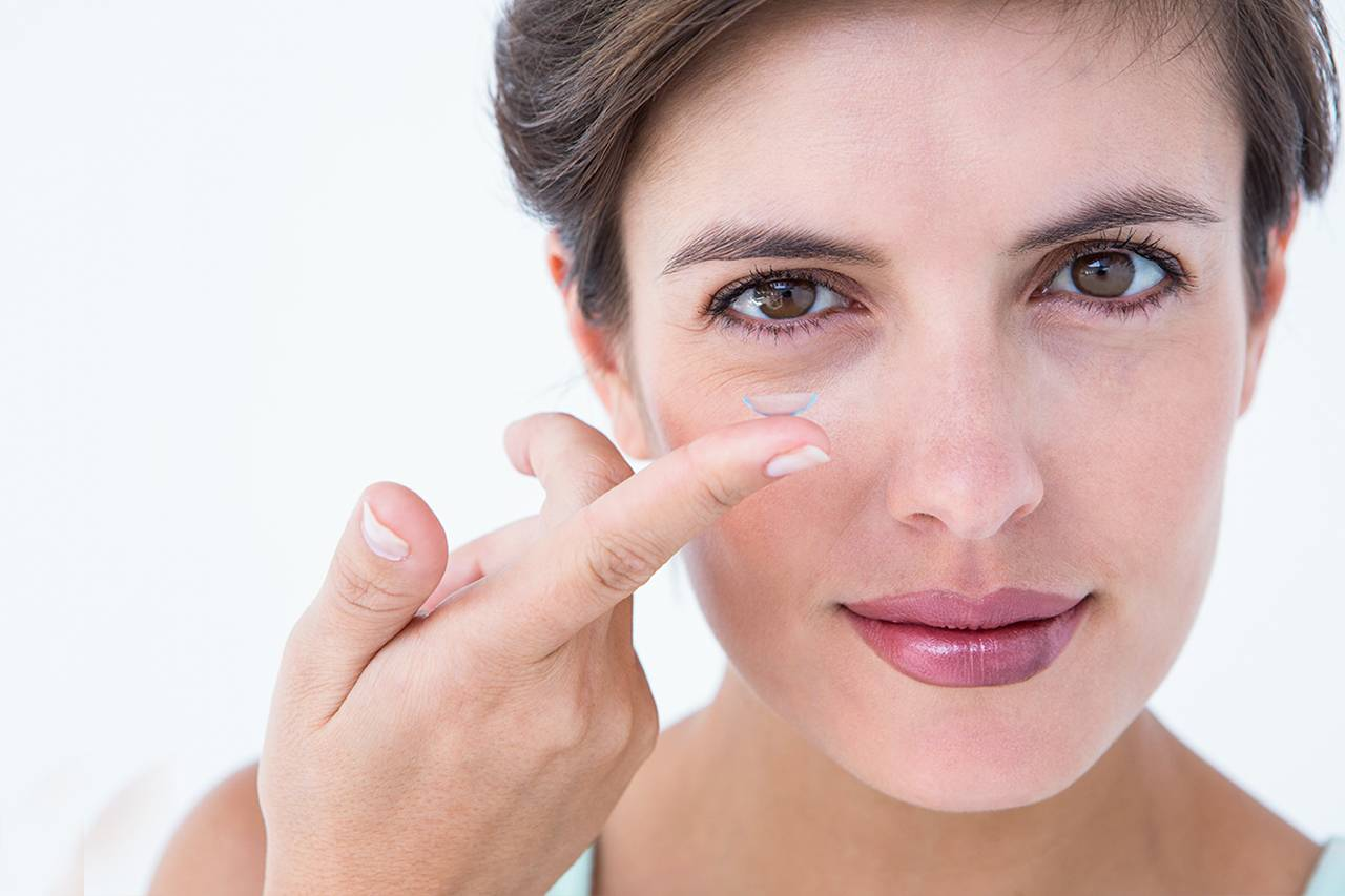 Photo of woman with contact lens on finger