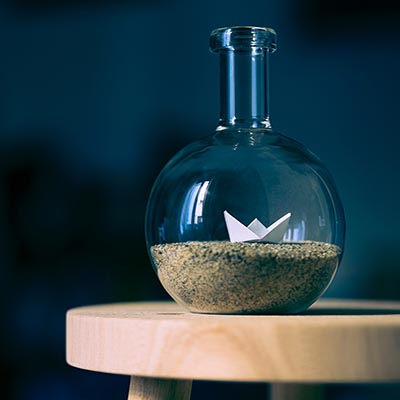 Beaker with sand and origami inside