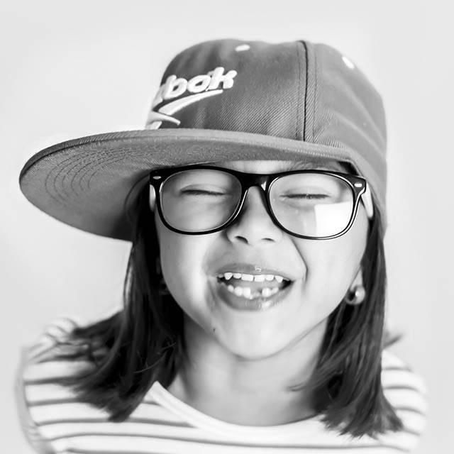 Young girl wearing eye glasses and laughing