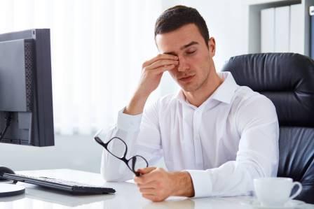 man rubbing eyes at computer, eye doctor, Kissimmee,Lakeland, FL