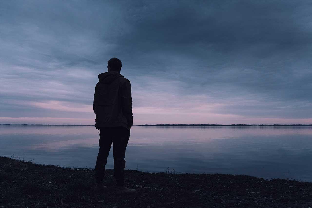 Man thinking, in shadow, alone