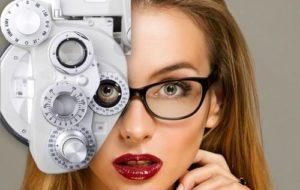 blonde woman, looking through phoropter while wearing eyeglasses