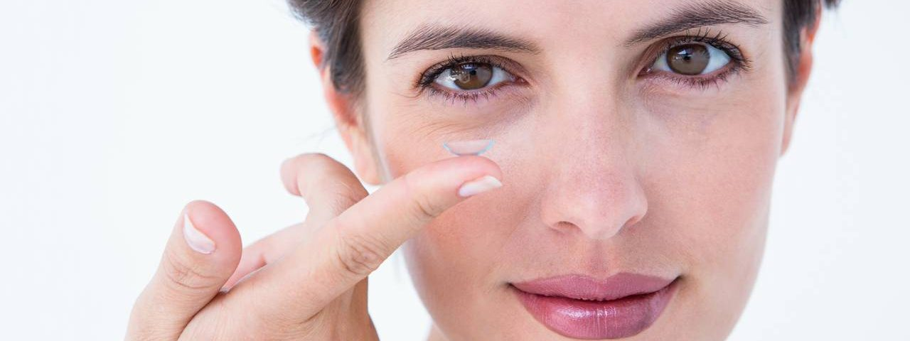 woman holding contact lens