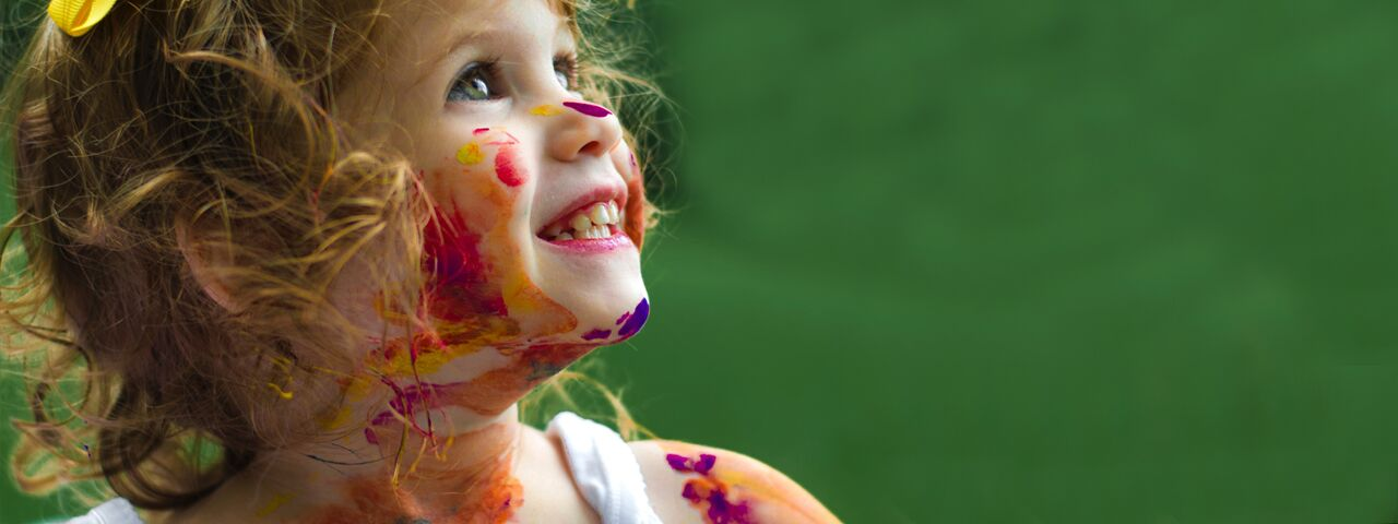 Blue-eyed little girl, with paint on face