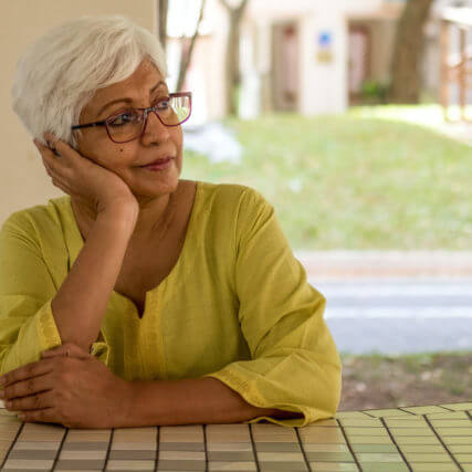 senior woman in eyeglasses sitting at a table