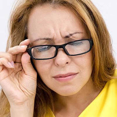 Woman, wearing eyeglasses, frowning