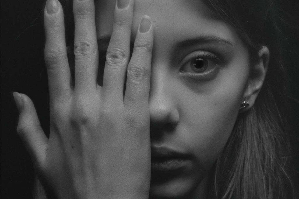 woman holding eye