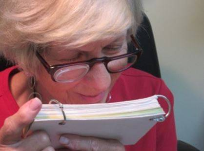 woman reading with low vision assistance device