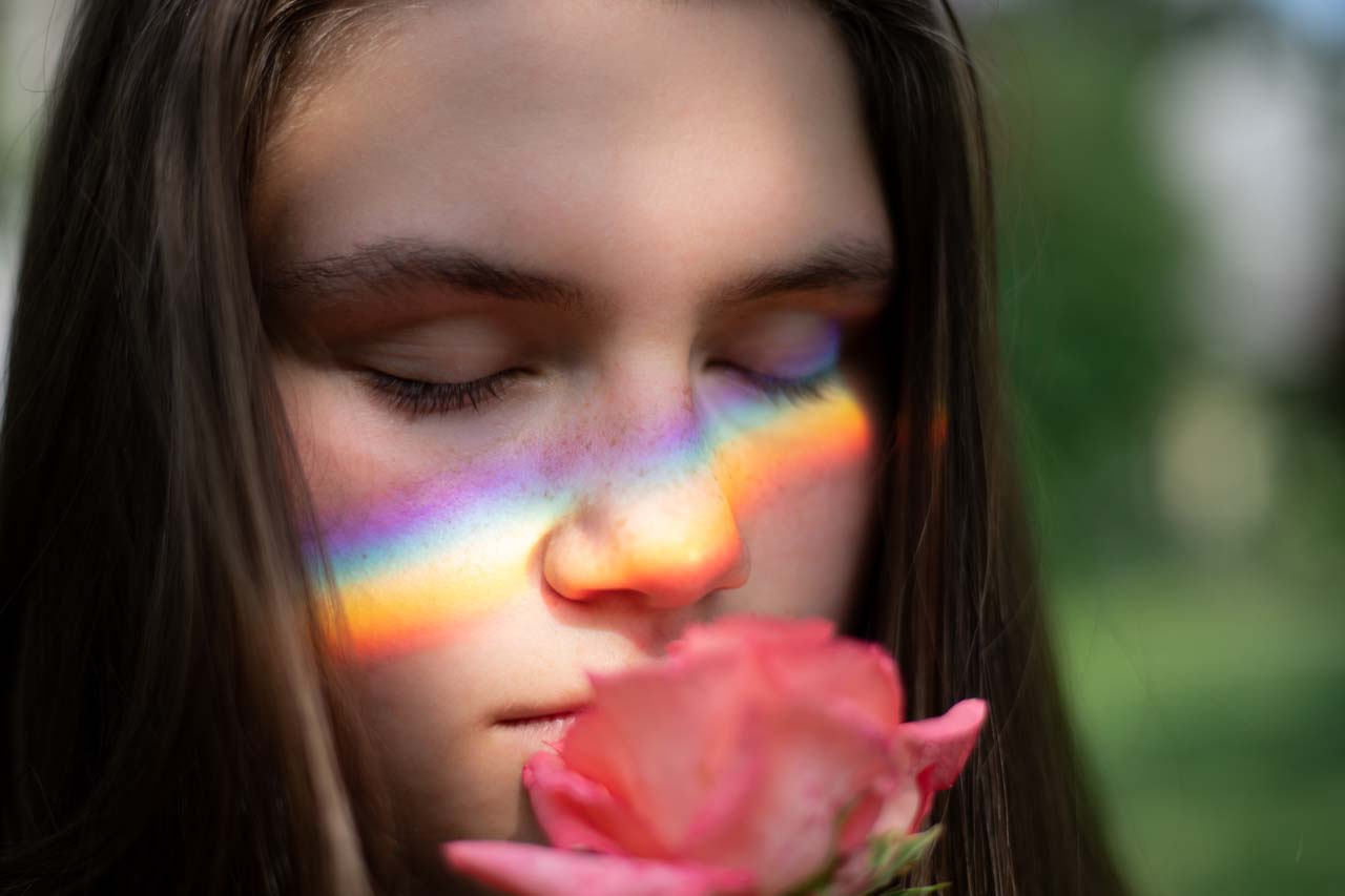 girl suffering vision loss, eyes closed, smelling rose