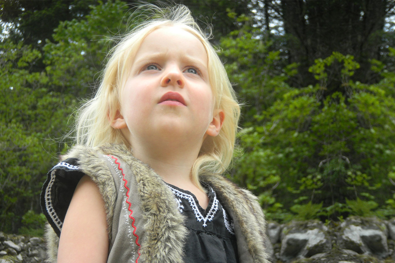 blonde child with blue eyes, looking to sky