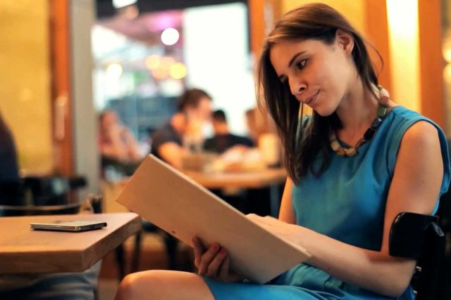 young woman with convergence insufficiency reading restaurant menu