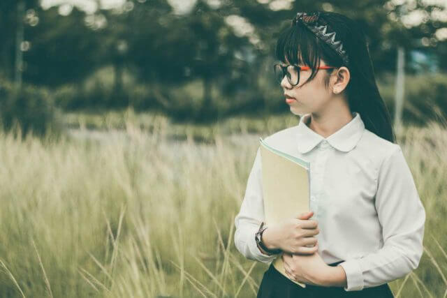 Female student wearing eyeglasses, carrying books