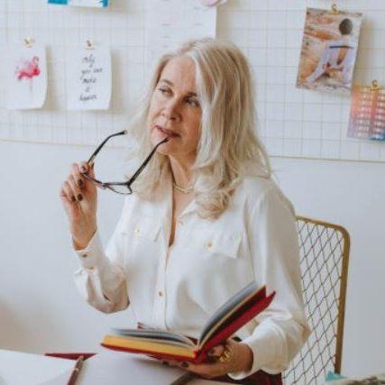 Caucasian senior woman holding eyeglasses reading a book