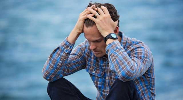man in blue and brown plaid dress shirt touching his hair 897817