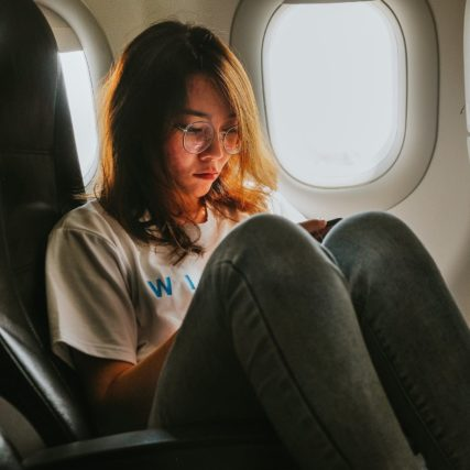 girl on cellphone in airplane e1606056089689.jpeg