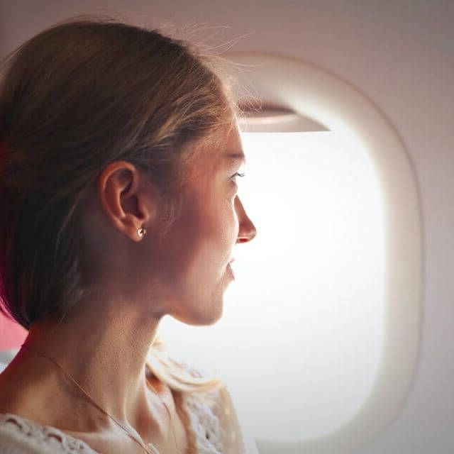 woman on airplane looking out window 640px