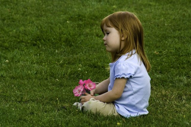 Young Girl Sitting in Grass
