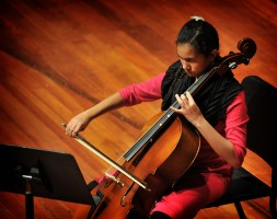 Female Community Music student plays cello in a recital