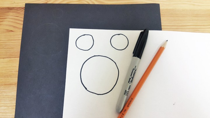 1. Cut out two small circles and one large circle out of the black paper that will fit inside the white circle pieces.