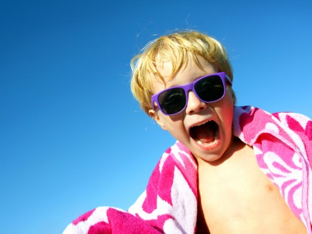 a young boy has a big smile on his face as he stands outside wrapped in a bright pink beach towel and wearing sunglasses, with a blue summer sky background.  room for text , copy space.