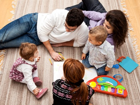 family group of five on the floor - two babies and three adults in the middle of a conversation.