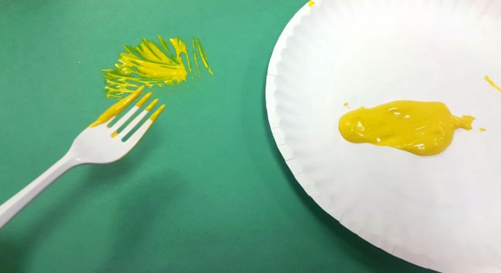 4 & 5. Pour a blob of paint onto the paper plate. Dip the fork into the paint and spread on the green construction paper in a rough, ball shape. The spike pattern from the fork should be visible to make the puffer fish spikes.