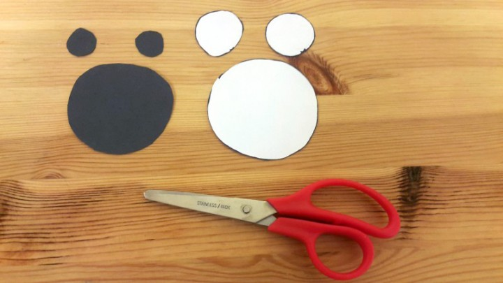 2. Cut out two small circles and one large circle out of the white paper for the eyes and mouth.