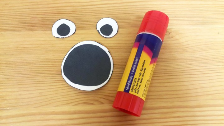 3. Glue the black circles to the corresponding white circles to make the eyes and the mouth.