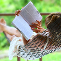 A woman reads a book while lying in a hammock.