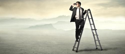 Man using binoculars to search desert - an exercise in futility