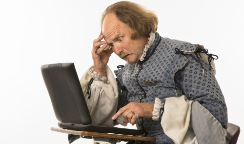 William Shakespeare lookalike sitting at computer