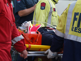 An accident victim is carried away on a stretcher