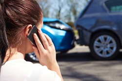 A woman makes a phone call following a rear-end auto accident